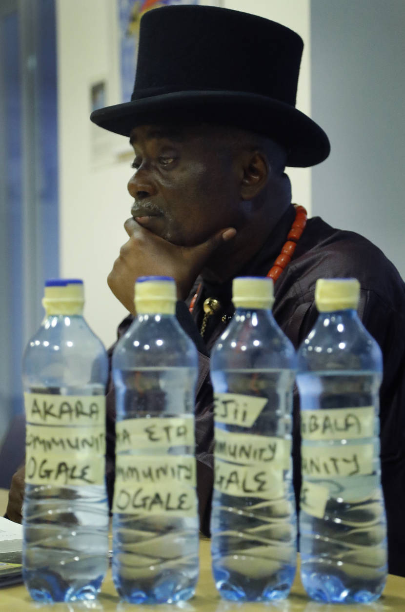 The King of Ogale, King Okpab, pauses behind some bottles with water samples of the Ogale area in Nigeria during an interview with The Associated Press in London, Monday, Nov. 21, 2016. Britain's High Court will begin hearing lawsuits on Tuesday filed by the Ogale and Bille people alleging that decades of oil spills have fouled the water and destroyed the lives of thousands of fishermen and farmers in the Niger River Delta. (AP Photo/Frank Augstein)