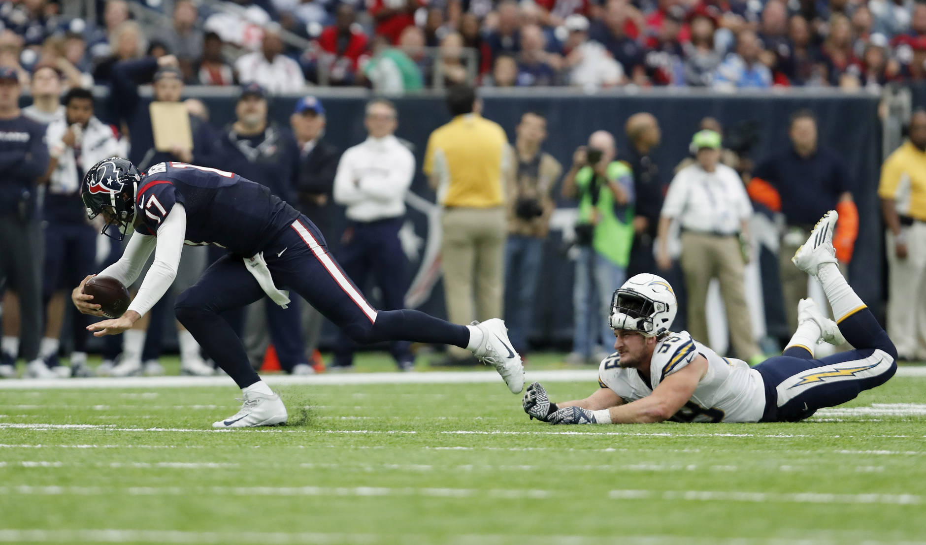 HOUSTON, TX - NOVEMBER 27:  Joey Bosa #99 of the San Diego Chargers loses his helmet as he trips up Brock Osweiler #17 of the Houston Texans in the fourth quarter at NRG Stadium on November 27, 2016 in Houston, Texas.  (Photo by Tim Warner/Getty Images)
