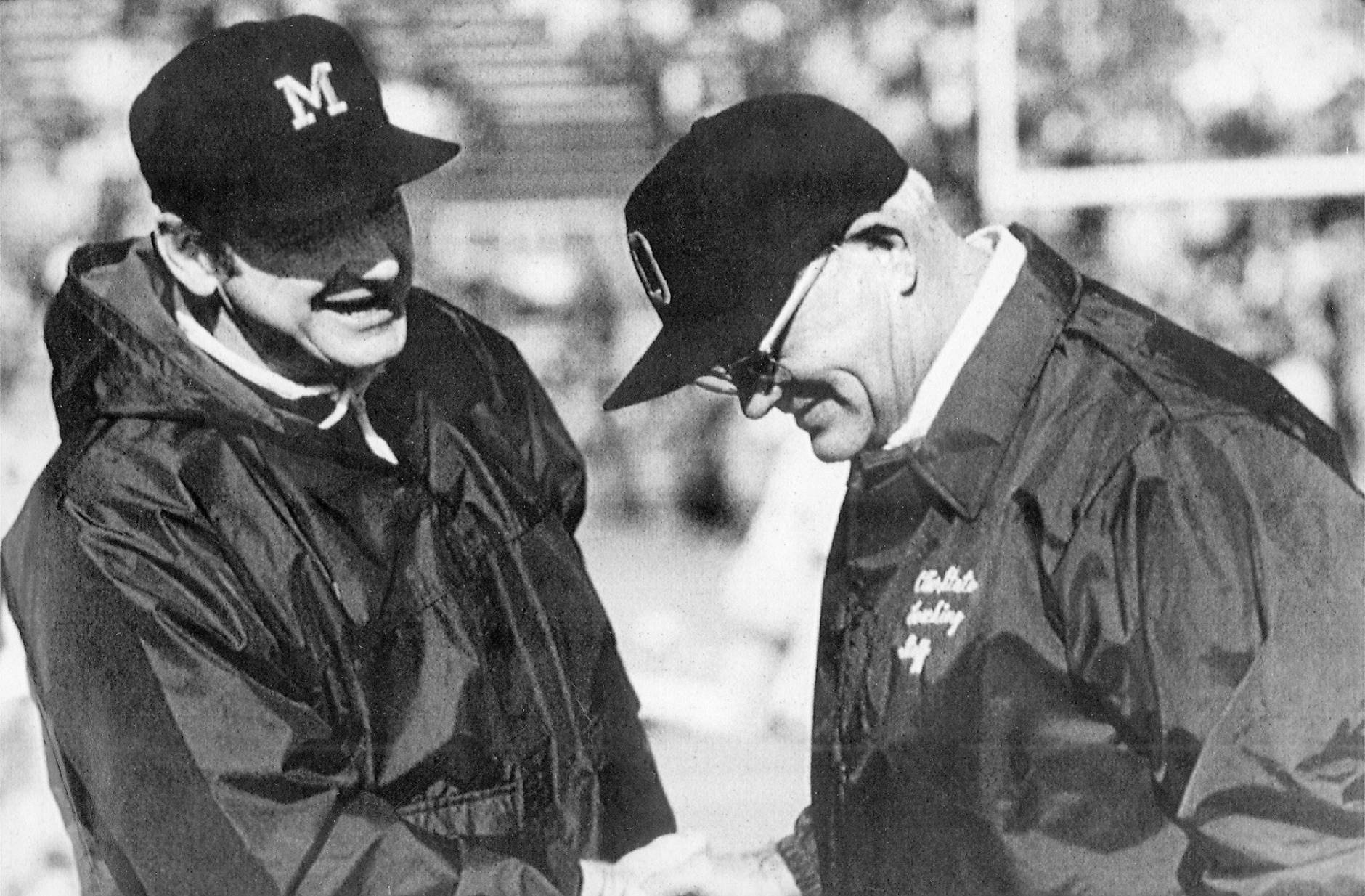 FILE - In this file photo, date and location not known, Michigan coach Bo Schembechler, left, meets with Ohio State coach Woody Hayes before an NCAA college football game. The story of the Ohio State-Michigan rivalry will always best be told through the tale of Woody and Bo. For 10 years, Woody Hayes' Buckeyes and Bo Schembechler's Wolverines reigned over the Big Ten and captivated the country. Teacher vs. pupil. Dear friends and fierce competitors, their legacies are intrinsically linked. (AP Photo, File)