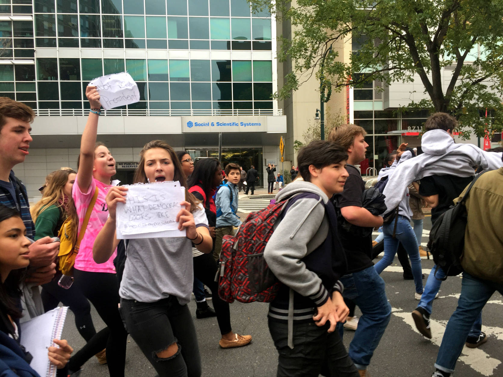 """A protester on Georgia Avenue in Silver Spring, Maryland holds sign up as she and her classmates chant """"He's not my president."""" The students were part of a massive protest against President-elect Donald Trump held Nov. 14, 2016. (WTOP/Megan Cloherty)"""