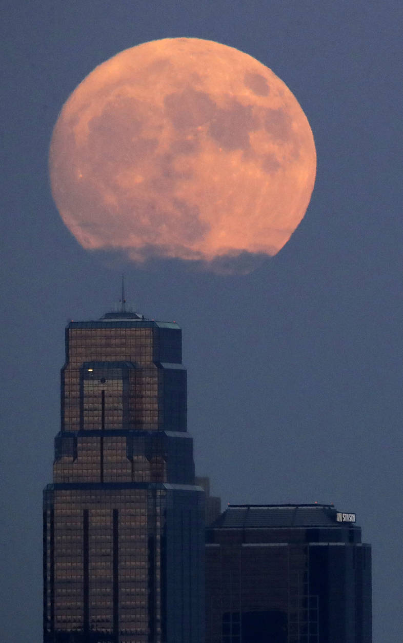 The moon rises beyond downtown buildings Sunday, Nov. 13, 2016, in Kansas City, Mo. Monday's so-called supermoon will be extra super - it will be the closest the moon comes to us in almost 69 years. And it won't happen again for another 18 years. (AP Photo/Charlie Riedel)