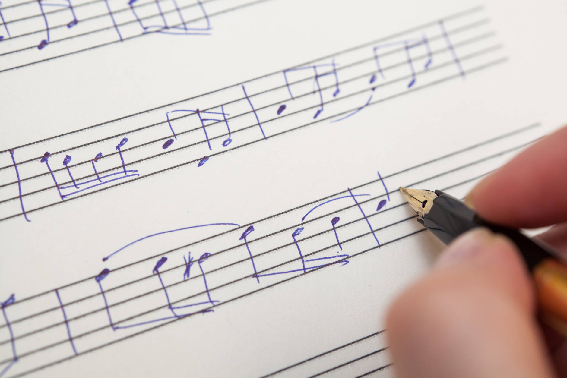 Hand pointing with pen to music book with handwritten notes