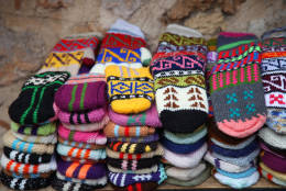 Bright mittens and socks with an ornament on a background of a stone wall