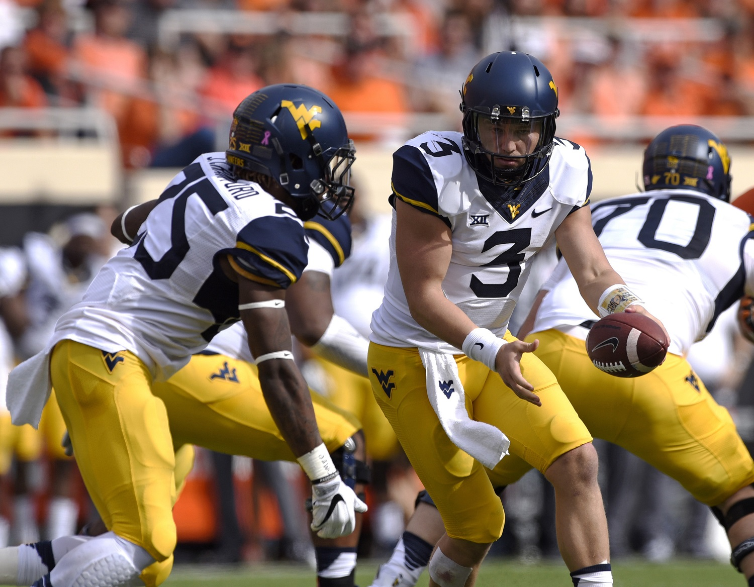FILE - In this Oct. 29, 2016, file photo, West Virginia quarterback Skyler Howard (3) hands off to running back Justin Crawford during the team's NCAA college football game against Oklahoma State in Stillwater, Okla. West Virginia travels to play Texas this week. (AP Photo/Brody Schmidt, File)