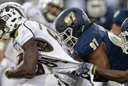 Western Michigan receiver Corey Davis, left, is grabbed by Akron defensive linemen Brennan Williams (97) and linebacker Ulysses Gilbert III in the fourth quarter of an NCAA college football game on Saturday, Oct. 15, 2016, in Akron, Ohio. (AP Photo/David Dermer)