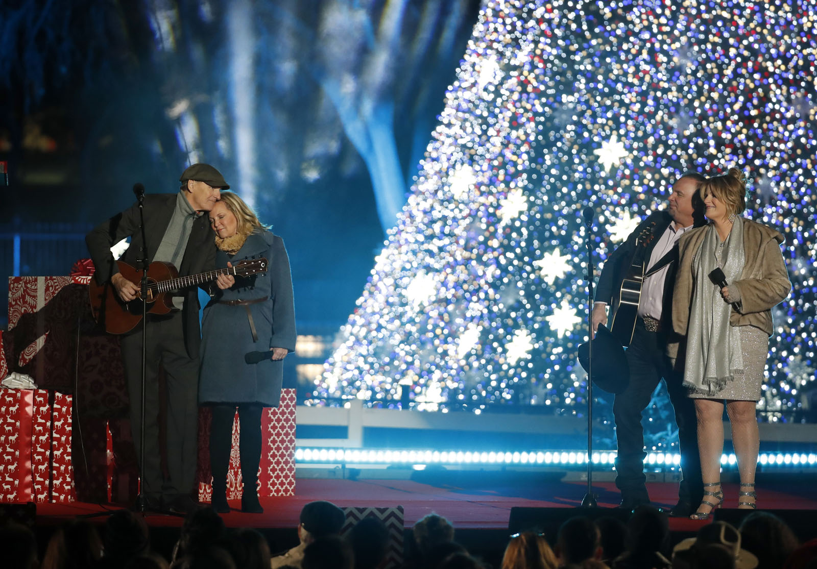 """James Taylor, left, with his wife Caroline """"Kim"""" Smedvig, Garth Brooks, and Tricia Yearwood perform during the lighting ceremony for the 2016 National Christmas Tree on the Ellipse near the White House, Thursday, Dec. 1, 2016 in Washington. (AP Photo/Alex Brandon)"""