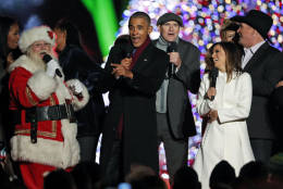 """President Barack Obama, sings """"Jingle Bells,"""" with Santa Claus, James Taylor, Eva Longoria, and Garth Brooks during the lighting ceremony for the 2016 National Christmas Tree on the Ellipse near the White House, Thursday, Dec. 1, 2016 in Washington. (AP Photo/Alex Brandon)"""