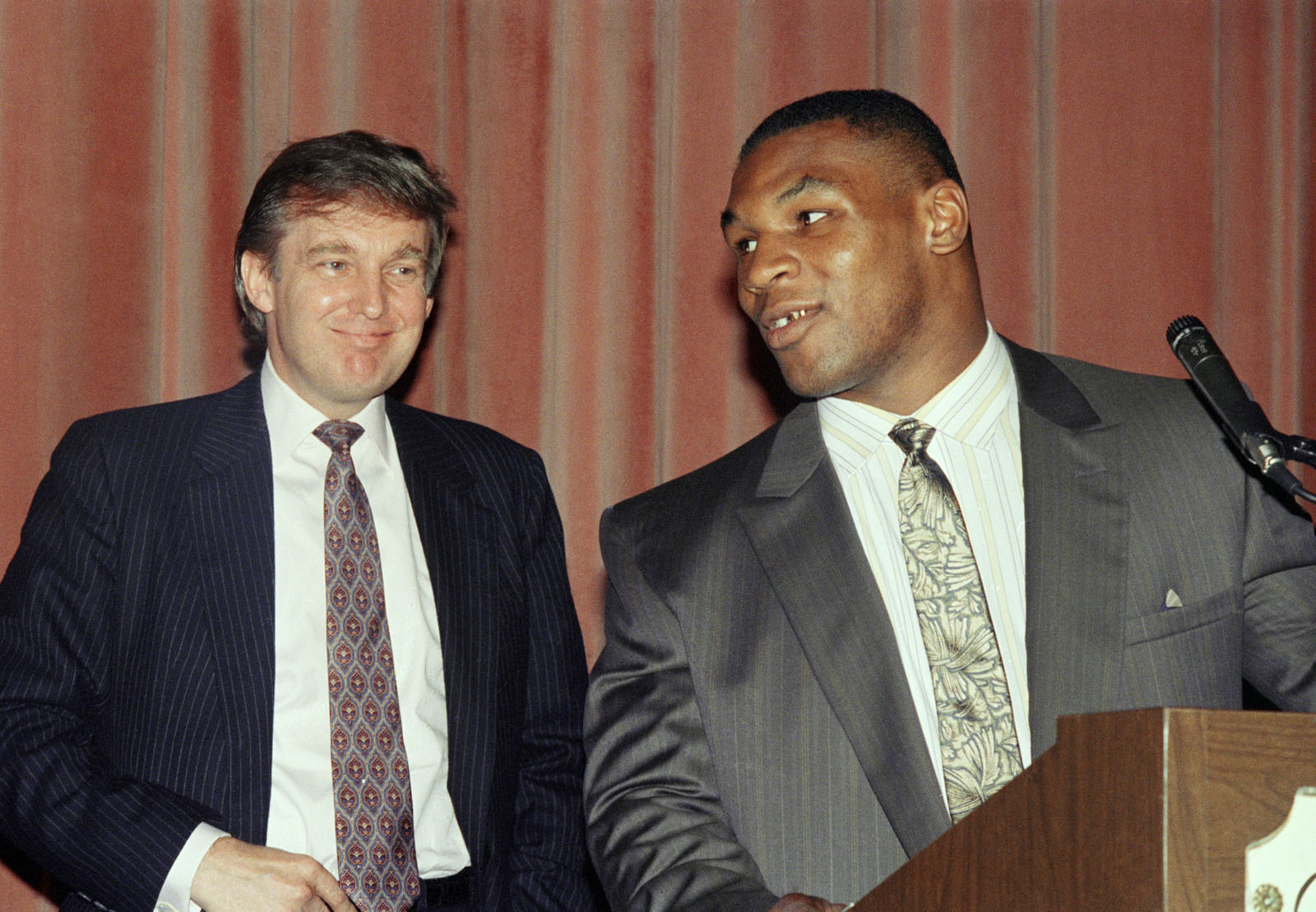 Heavyweight champion Mike Tyson, right, speak at a news conference while advisor Donald Trump looks in New York, Tuesday, July 27, 1988 after announcing a settlement between Tyson and his manager, Bill Cayton. Tyson, who had sued to break his contract with Cayton, reached an ou-of-court settlement under which Cayton will remain his manager until Feb. 11, 1992. (AP Photo/Richard Drew)