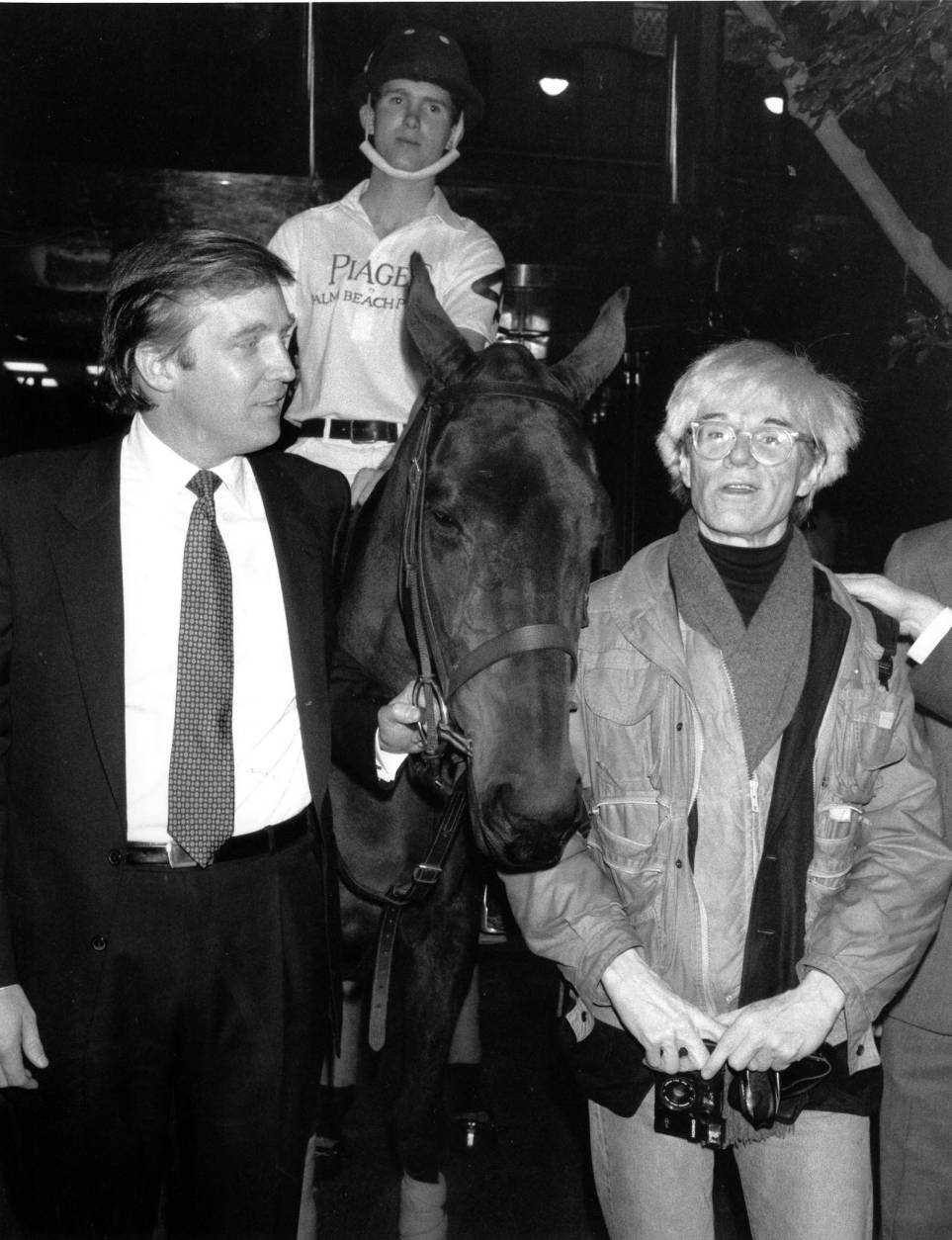 Donald Trump owner of New York's Trump Tower, holds the bridle of a polo pony while talking to Andy Warhol on Nov. 4, 1983.  Yale University polo player Eric Stever sits astride the horse.  (AP Photo/Mario Suriani)