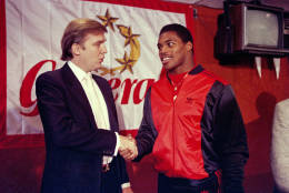 FILE - In this March 8, 1984, file photo, then-New Jersey Generals owner Donald Trump, left, shakes hands with Herschel Walker at a press conference in New York, after agreeing on a 4-year contract. Retired NFL player Herschel Walker says he's being dropped from speaking engagements because of his relationship with Donald Trump. (AP Photo/Dave Pickoff, File)