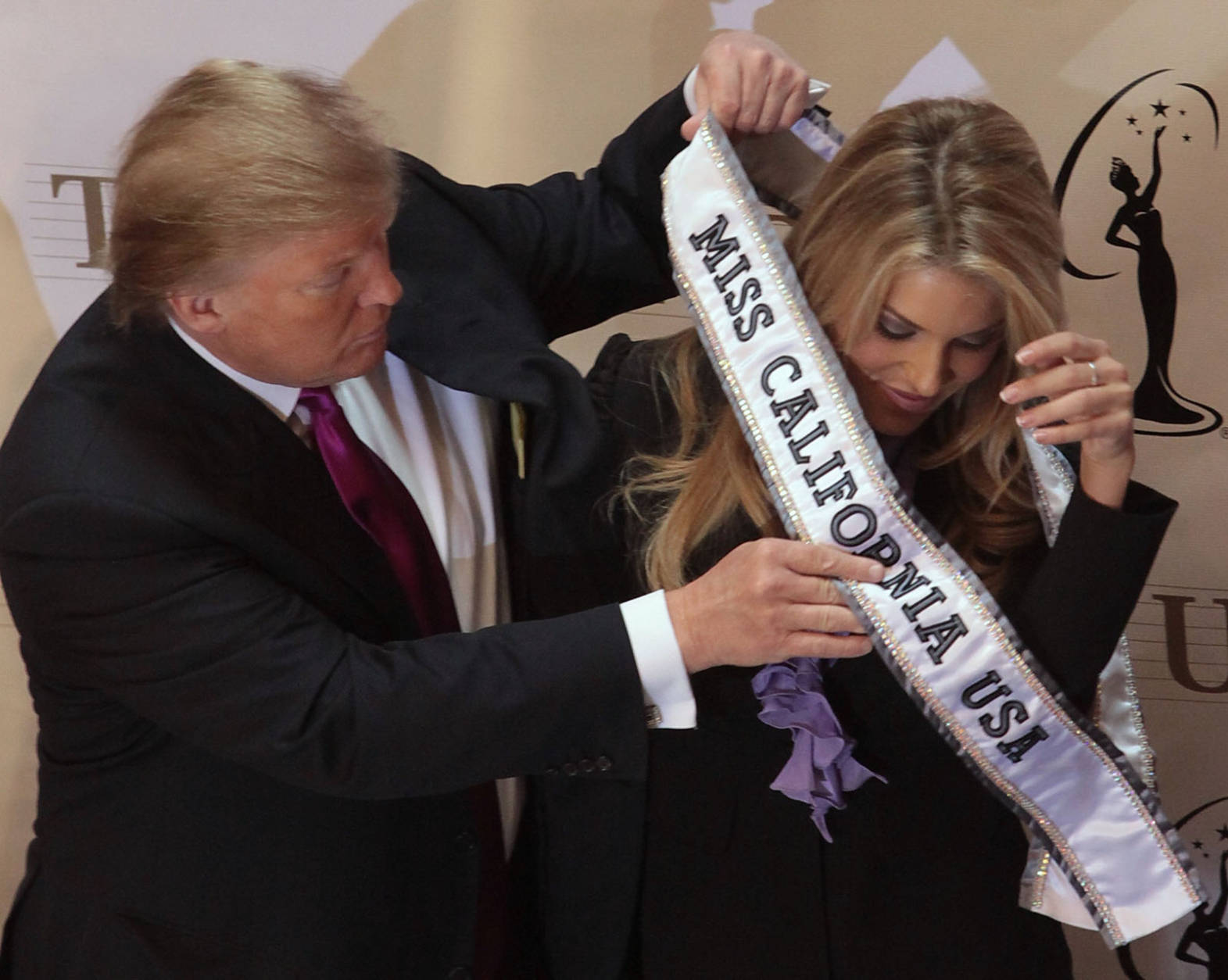 Donald Trump place a sash on Miss California USA, Carrie Prejean following a news conference in New York, Tuesday May 12, 2009.  Trump, who owns the Miss USA pageant, says Prejean can retain her Miss California USA crown after she caused a stir expressing opposition to gay marriage and posing in risque photographs.  (AP Photo/Bebeto Matthews)