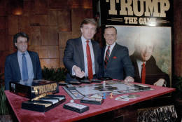 """Real estate mogul Donald Trump, left, takes his turn as George Ditomassi, president of the Milton Bradley company, looks on at a news conference in New York, announcing a new board game, """"Trump, The Game,"""" Feb. 7, 1989. The game allows players to bid against each other and make deals for big ticket real estate. Man at far left is unidentified. (AP Photo/Mario Suriani)"""