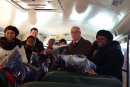 Volunteers and Prince George's County Public Schools CEO Kevin Maxwell loaded up a school bus with new coats for more than 300 homeless students. The coats were donated by the Shops at Iverson. (WTOP/Kathy Stewart)