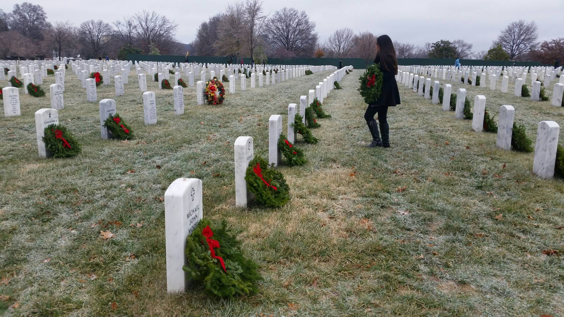 A woman stands in Arlington Cemetery, where the 25th annual Wreaths Across America ceremony to honor veterans took place on an icy morning Dec. 17, 2016. (WTOP Kathy Stewart)