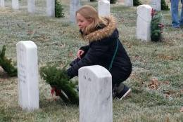 A woman lay a wreath at a grave in Arlington Cemetery, where the 25th annual Wreaths Across America ceremony to honor veterans took place on an icy Saturday morning, Dec. 17, 2016. (WTOP Kathy Stewart)