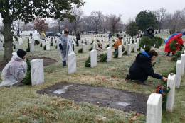 Despite icy road conditions and a winter weather advisory, 44,000 volunteers showed up at Arlington Cemetery to lay wreaths to honor veterans Saturday morning, Dec. 17, 2016. (WTOP Kathy Stewart)