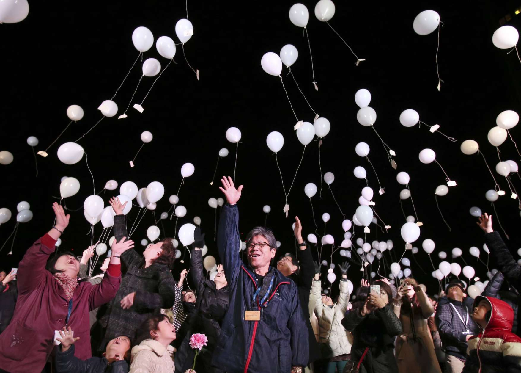 People release balloons into the air to celebrate New Year, during a New Year celebration event at a Tokyo Hotel, early Sunday, Jan. 1, 2017. (AP Photo/Koji Sasahara)