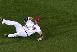 Washington Nationals right fielder Bryce Harper slides on the field after he caught a fly ball by Miami Marlins' J.T. Realmuto for an out during the third inning of a baseball game, Friday, Sept. 30, 2016, in Washington. (AP Photo/Nick Wass)