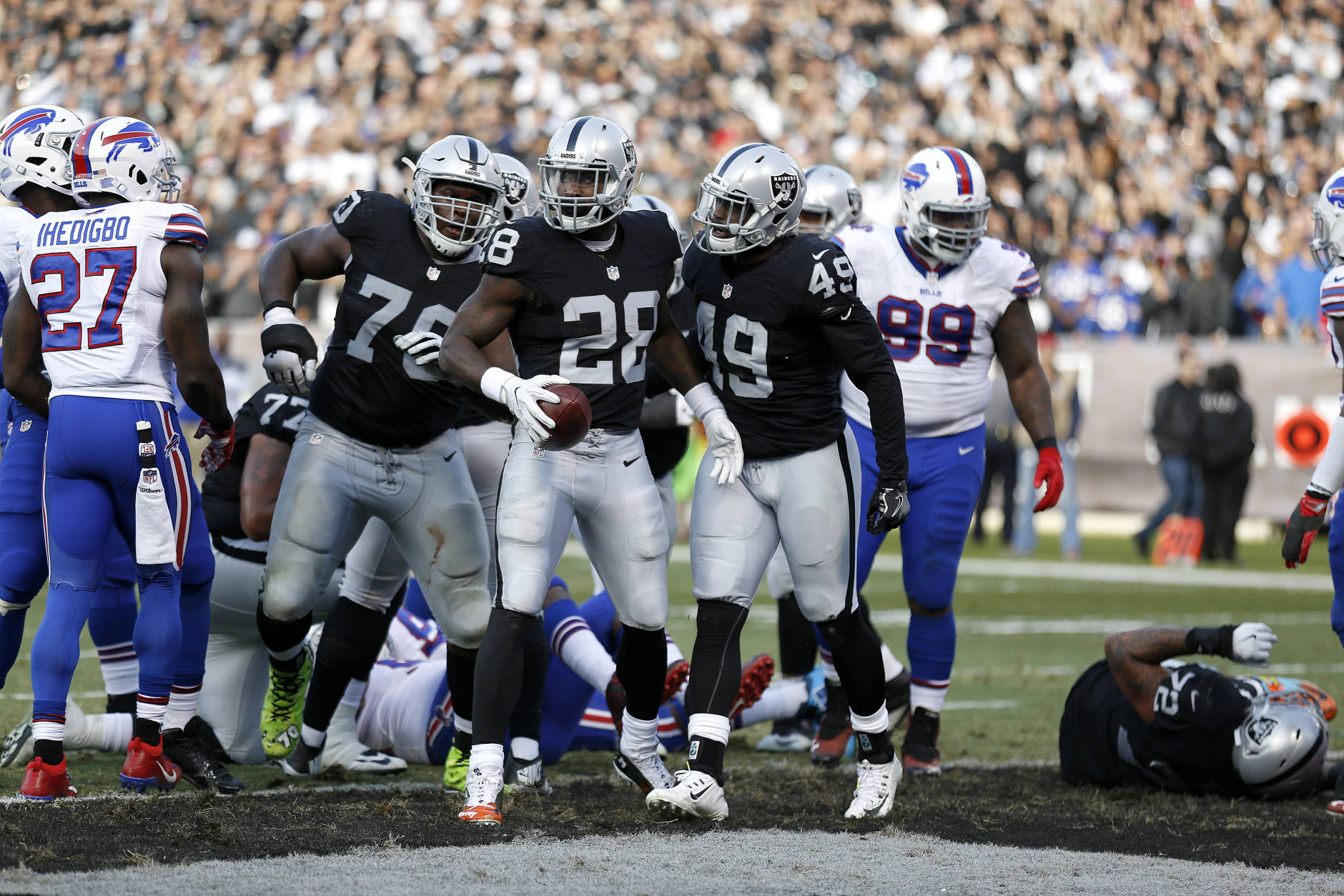 Oakland Raiders running back Latavius Murray (28) celebrates after running for a touchdown with running back Jamize Olawale (49) and offensive guard Kelechi Osemele (70) against the Buffalo Bills during the second half of an NFL football game in Oakland, Calif., Sunday, Dec. 4, 2016. (AP Photo/D. Ross Cameron)