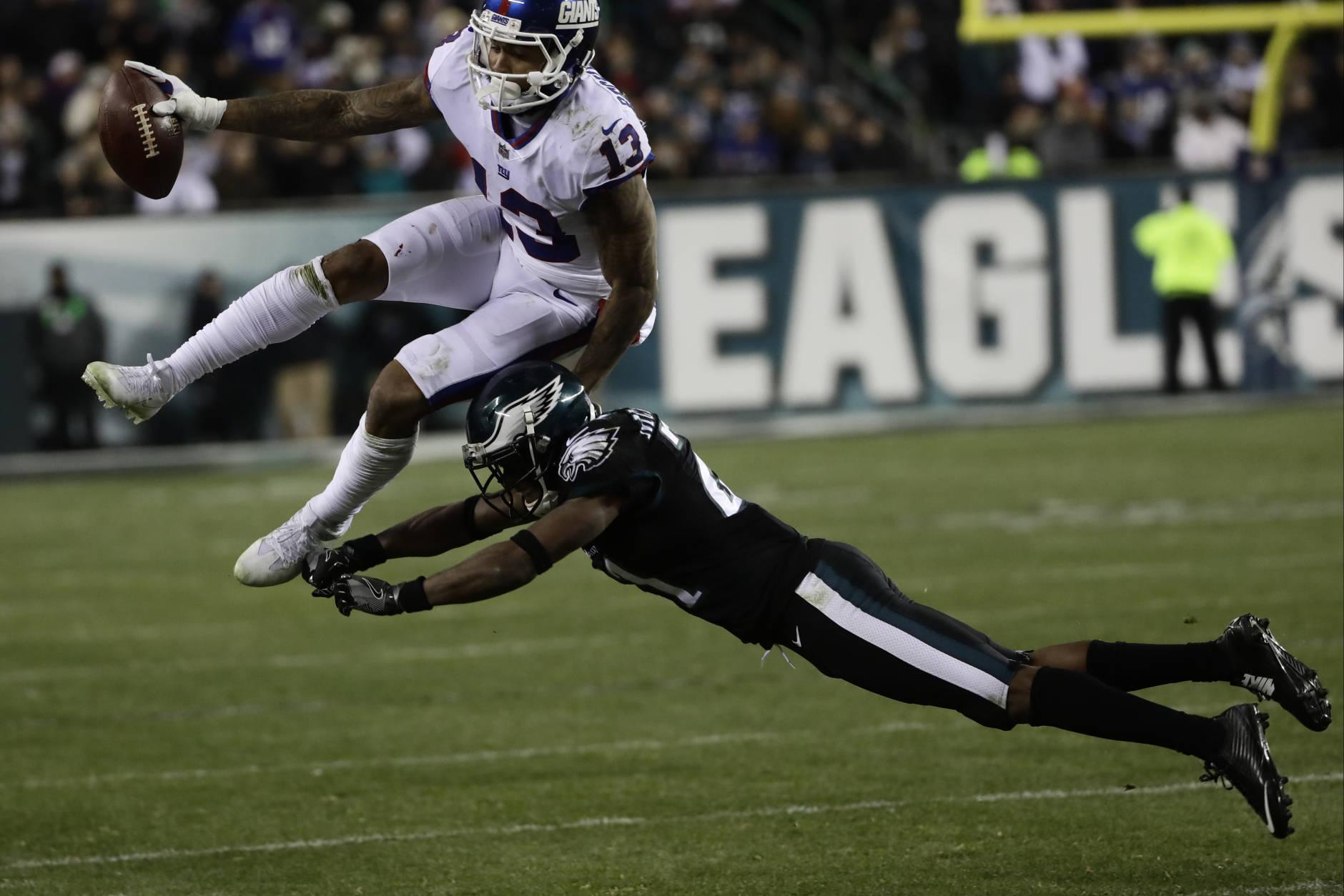 New York Giants' Odell Beckham (13) is hit by Philadelphia Eagles' Leodis McKelvin (21) during the second half of an NFL football game, Thursday, Dec. 22, 2016, in Philadelphia. (AP Photo/Michael Perez)
