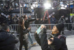 Visitors to Times Square take photos as technicians prepare a stage that will be used in the New Years celebration, Friday, Dec. 30, 2016, in New York's Times Square. (AP Photo/Mary Altaffer)