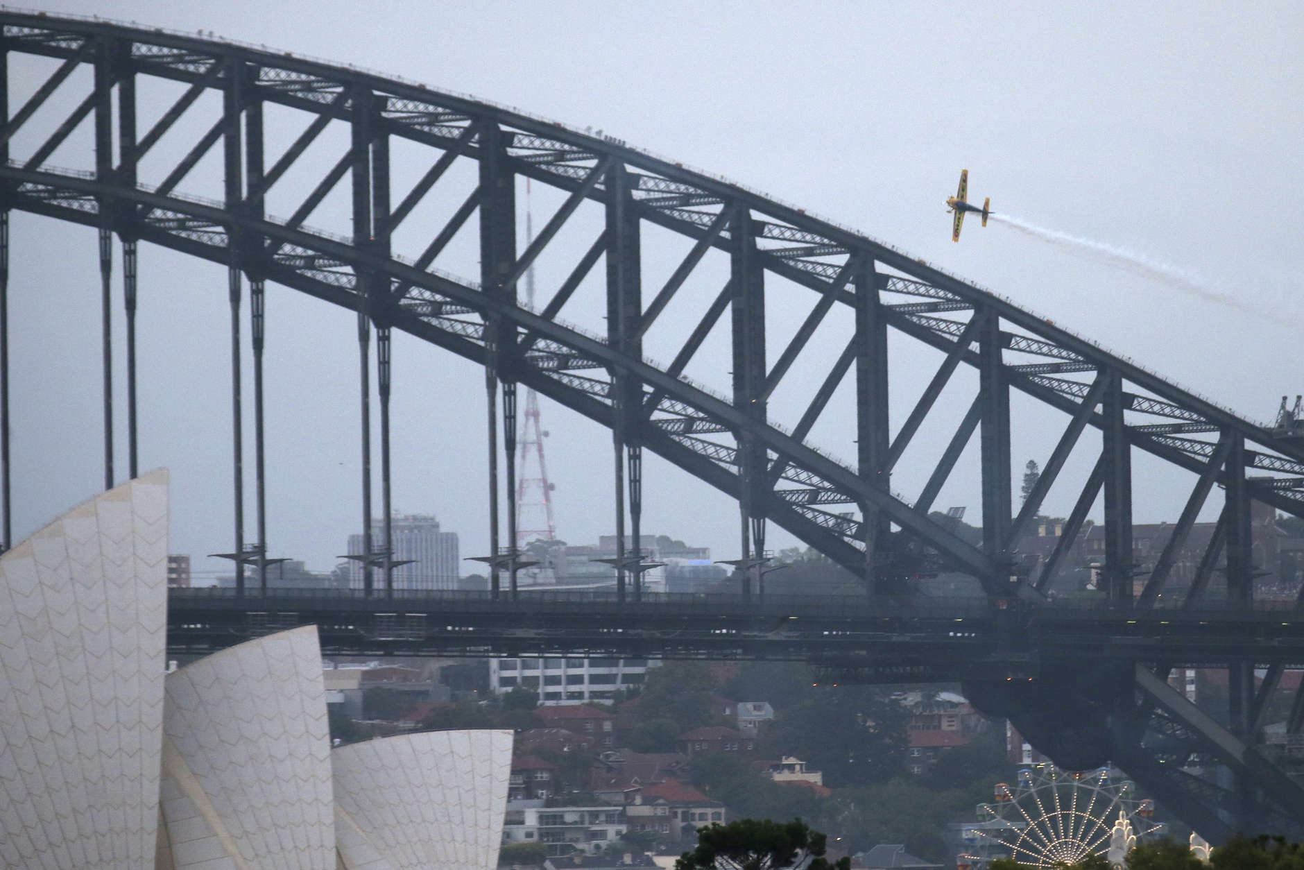 An acrobatic plane maneuvers around the Sydney Opera House and Harbour Bridge as New Year's celebrations get underway in Sydney, Australia, Saturday, Dec. 31, 2016. (AP Photo/Rick Rycroft)
