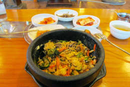 This February 2014 photo shows a traditional Korean dinner of bibimbap, a dish made of rice, sliced beef, vegetables and chilies, accompanied by several smaller plates of pickles and kimchi in Seoul, Korea. Seoul's hyper-efficient capital draws visitors with its exquisite restaurants, historic palaces and ultramodern infrastructure. (AP Photo/Amir Bibawy).