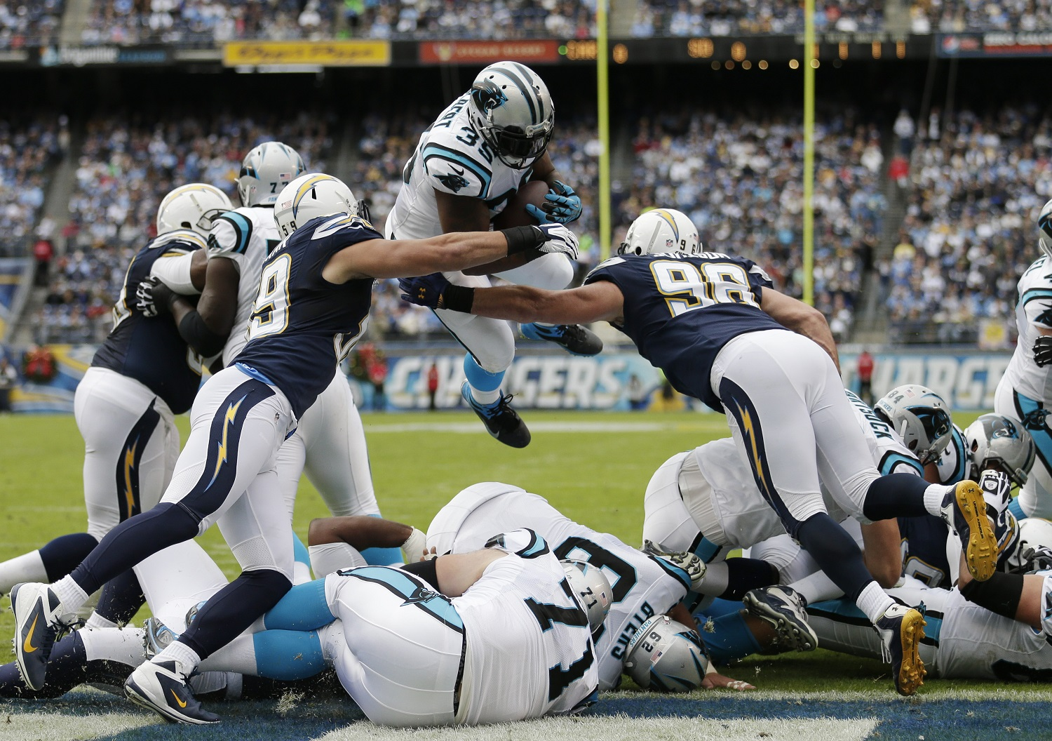 Carolina Panthers fullback Mike Tolbert  sails over the top of the San Diego Chargers defense to score a touchdown during the first half of a NFL football game Sunday, Dec. 16, 2012, in San Diego. (AP Photo/Gregory Bull)