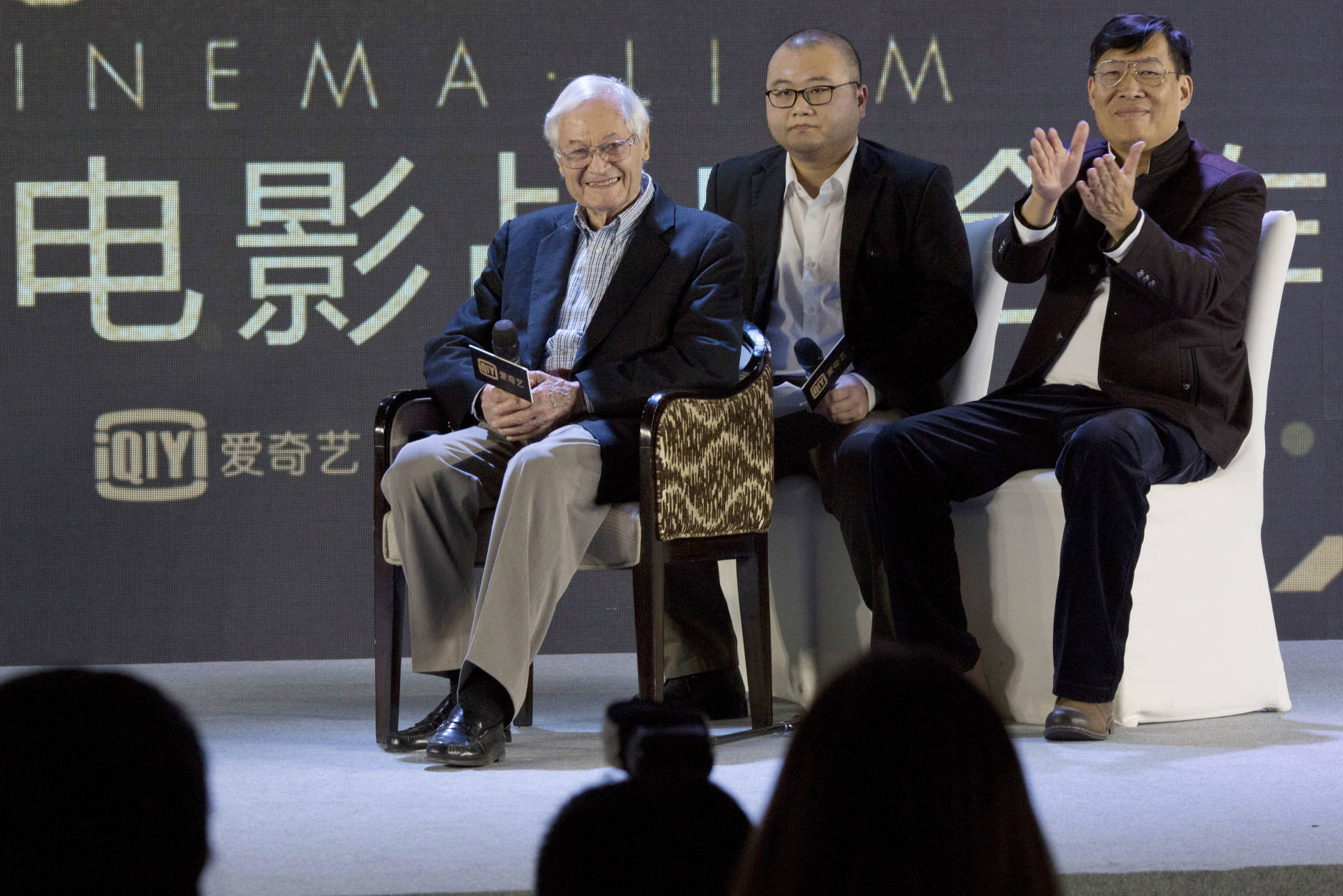 "American film producer Roger Corman, left, attends a news conference to announce co-production between Chinese online video site iQIYI and Sony Pictures in Beijing, China, Thursday, Dec. 1, 2016. The 90-year-old American producer of films including ""The St. Valentine's Day Massacre"" and ""Attack of the 50 Foot Cheerleader"" will lead a team of young Chinese filmmakers and act as producer on a sci-fi film made for viewing on the internet or mobile phone called ""Invasion."" (AP Photo/Ng Han Guan)"