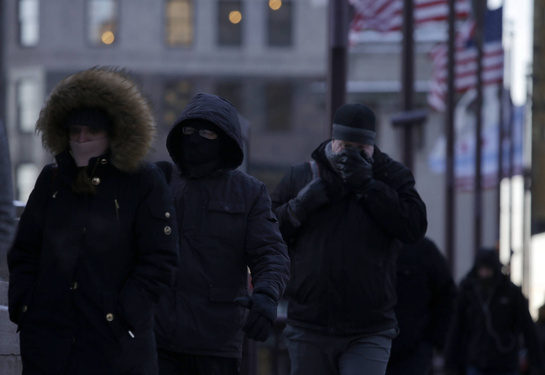 Morning commuters bundle up, Thursday, Dec. 15, 2016, in Chicago. Dangerously cold temperatures gripped the Upper Midwest in advance of a storm that's expected to bring several inches of snow in coming days, while schools and officials in the Northeast braced for their own blast of wintry weather. (AP Photo/Kiichiro Sato)