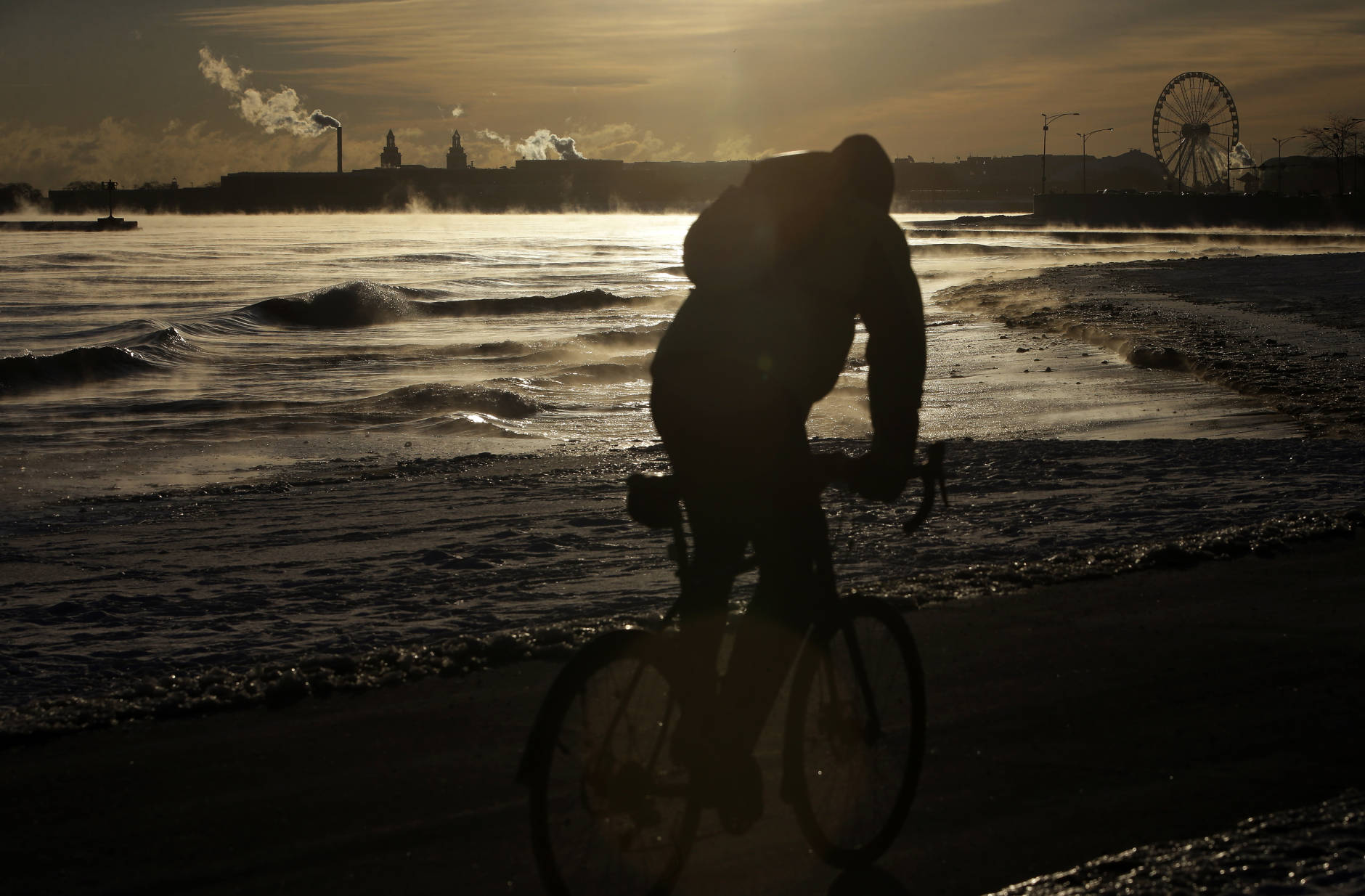 A bike commuter rides along Lake Michigan, Thursday, Dec. 15, 2016, toward downtown Chicago. Dangerously cold temperatures gripped the Upper Midwest in advance of a storm that's expected to bring several inches of snow in coming days.  (AP Photo/Kiichiro Sato)