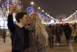 A man takes a picture as he kisses his companion during the New Year's Eve celebration on the Champs Elysees, in Paris, France, Sunday, Jan.1, 2017. (AP Photo/Christophe Ena)