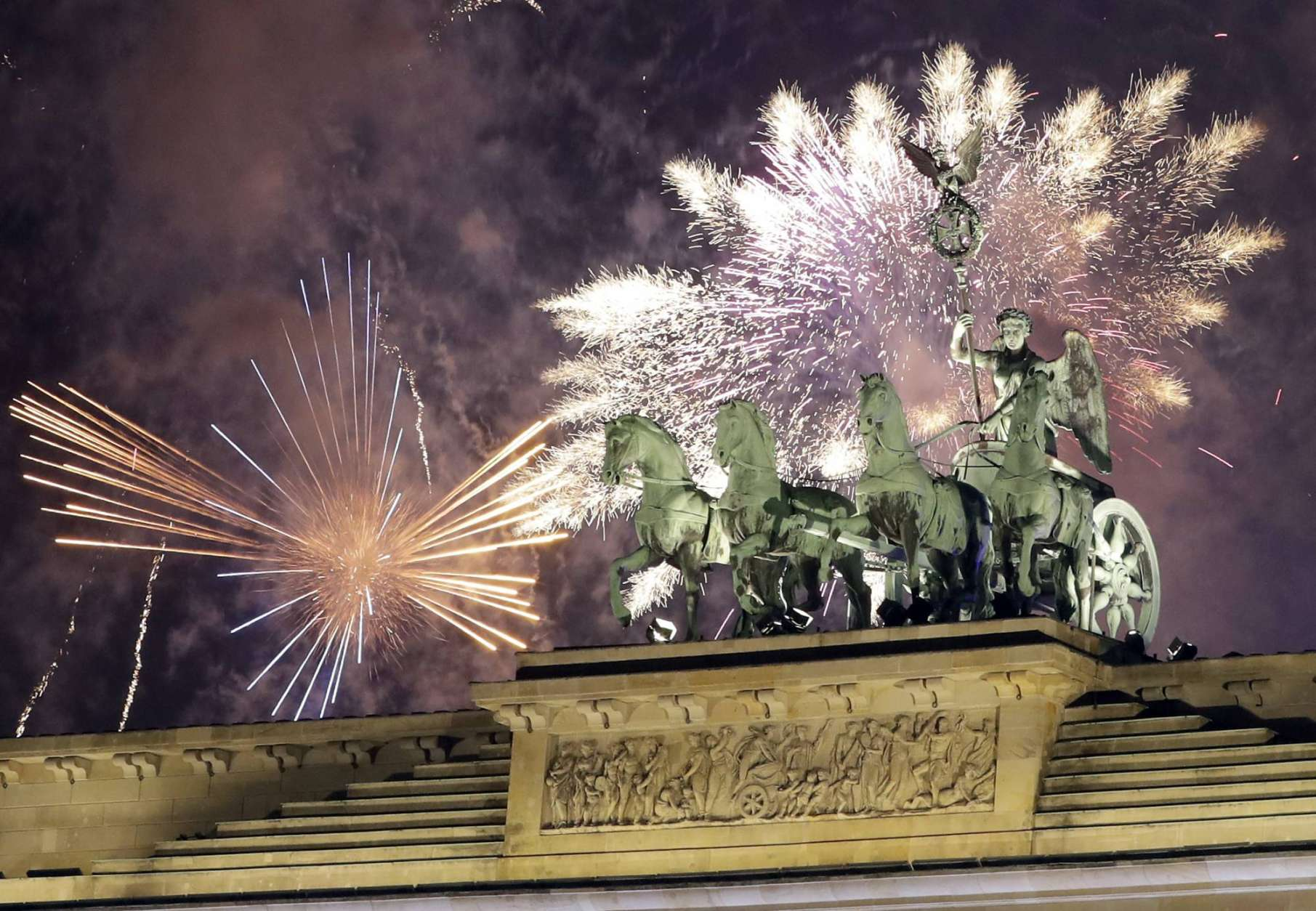 Fireworks light the sky above the Quadriga at the Brandenburg Gate shortly after midnight in Berlin, Germany, Sunday, Jan. 1, 2017. Hundred thousands of people celebrated New Year's Eve welcoming the new year 2017 in Germany's capital. (AP Photo/Michael Sohn)