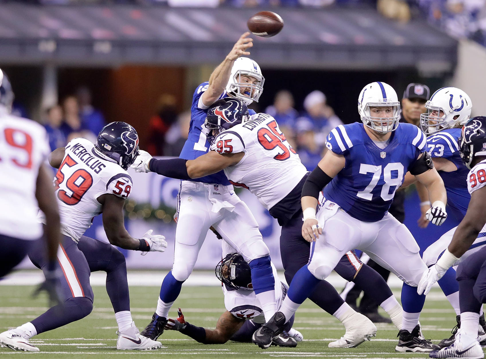 INDIANAPOLIS, IN - DECEMBER 11:  Quarterback Andrew Luck #12 of the Indianapolis Colts is hit by Christian Covington #95 of the Houston Texans during the game at Lucas Oil Stadium on December 11, 2016 in Indianapolis, Indiana.  (Photo by Andy Lyons/Getty Images)