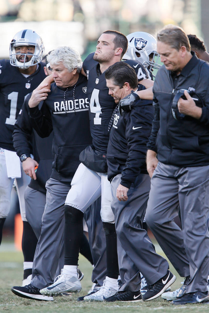 OAKLAND, CA - DECEMBER 24:  Derek Carr #4 of the Oakland Raiders is helped off the field after injuring his right leg during their NFL game against the Indianapolis Colts at Oakland Alameda Coliseum on December 24, 2016 in Oakland, California.  (Photo by Brian Bahr/Getty Images)