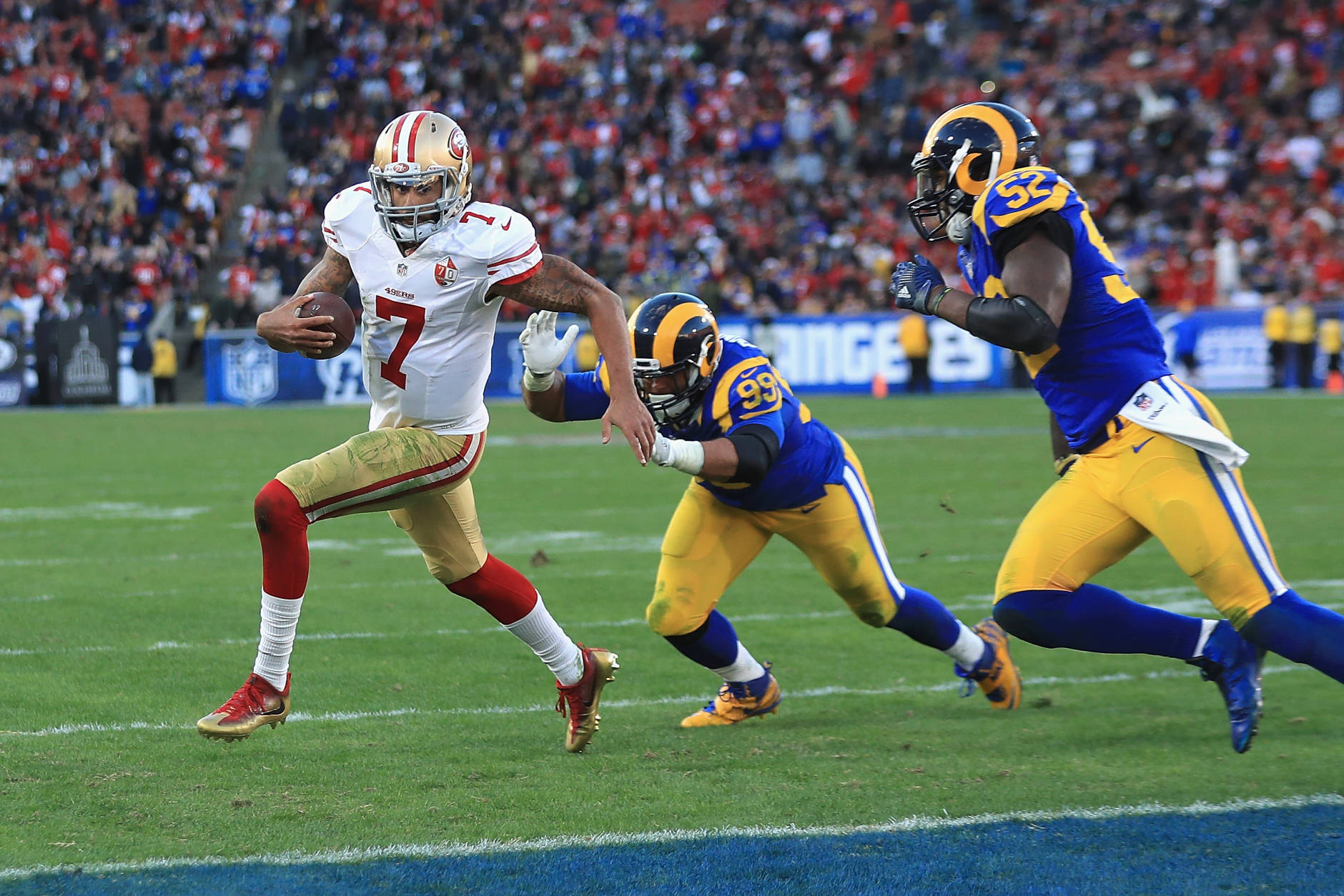 LOS ANGELES, CA - DECEMBER 24:  Colin Kaepernick #7 of the San Francisco 49ers rushes for a 13-yard touchdown during the fourth quarter as Aaron Donald #99 and Alec Ogletree #52 of the Los Angeles Rams attempt to tackle him at Los Angeles Memorial Coliseum on December 24, 2016 in Los Angeles, California.  (Photo by Sean M. Haffey/Getty Images)