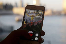 """FILE - In this July 25, 2016, file photo, a fan maneuvers his smartphone as he plays """"Pokemon Go"""" in Hong Kong. """"Pokemon Go"""" is among Google's most-trending searches of 2016. The search engine giant released its year end trending searches list on Dec. 14, 2016. (AP Photo/Kin Cheung, File)"""