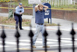Edgar Maddison Welch, 28 of Salisbury, N.C., surrenders to police Sunday, Dec. 4, 2016, in Washington. Welch, who said he was investigating a conspiracy theory about Hillary Clinton running a child sex ring out of a pizza place, fired an assault rifle inside the restaurant on Sunday injuring no one, police and news reports said. (Sathi Soma via AP)