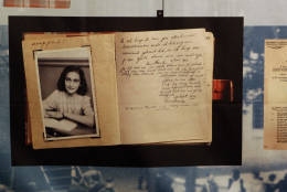 """FILE - This June 12, 2009 file photo, shows a photo of Anne Frank at the opening of the exhibition: """"Anne Frank, a History for Today"""", at the Westerbork Remembrance Centre in Hooghalen, northeast Netherlands. A new study by the Anne Frank House museum in Amsterdam said Friday, Dec. 16, 2016, there is no conclusive evidence that the Jewish diarist and her family were betrayed to the Netherlands' German occupiers during World War II, leading to their arrest and deportation. (AP Photo/Bas Czerwinski, File)"""