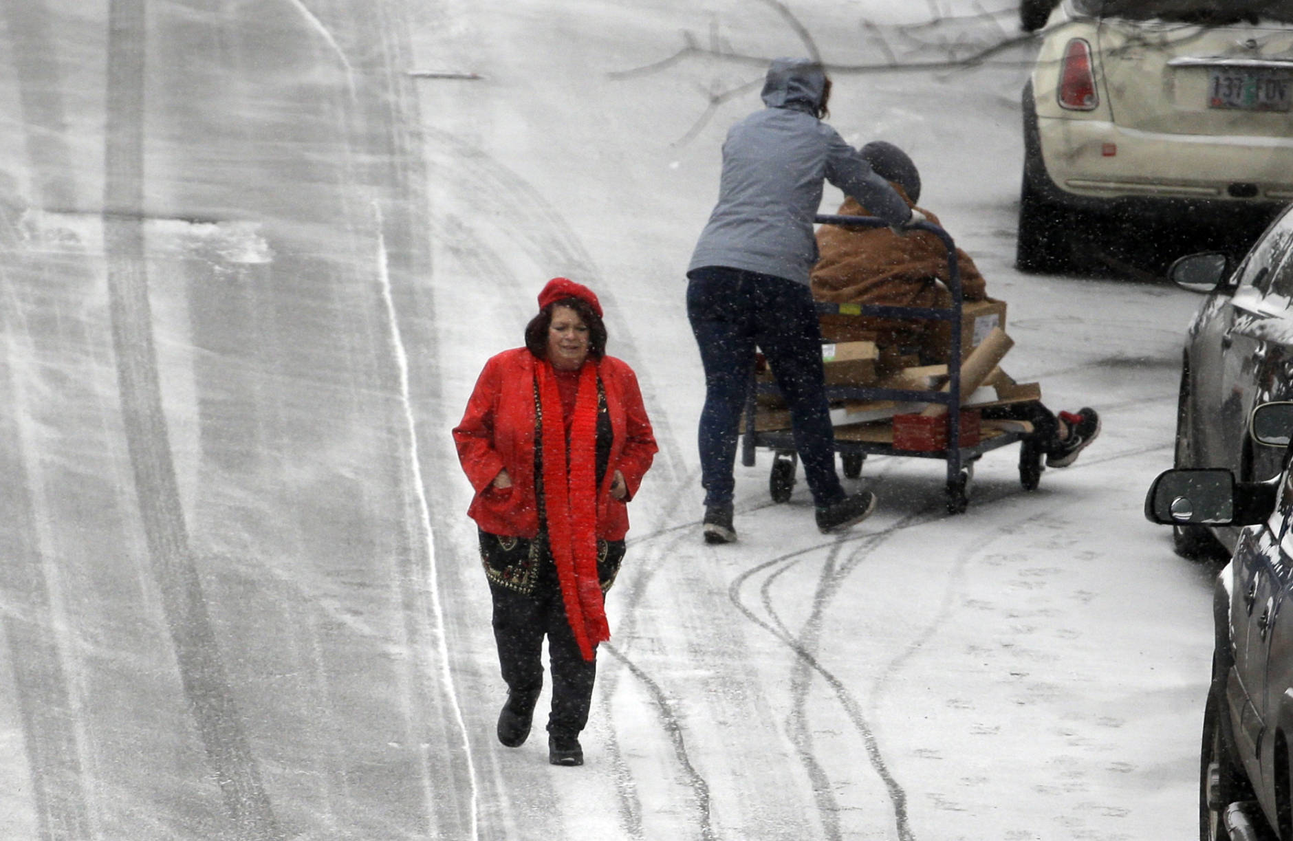 People maneuver on slick roads as a snow storm moves in on the area in Portland, Ore., Wednesday, Dec. 14, 2016. A wintry afternoon and evening is forecast for much of Oregon, with some cities expected to get a foot of snow.(AP Photo/Don Ryan)