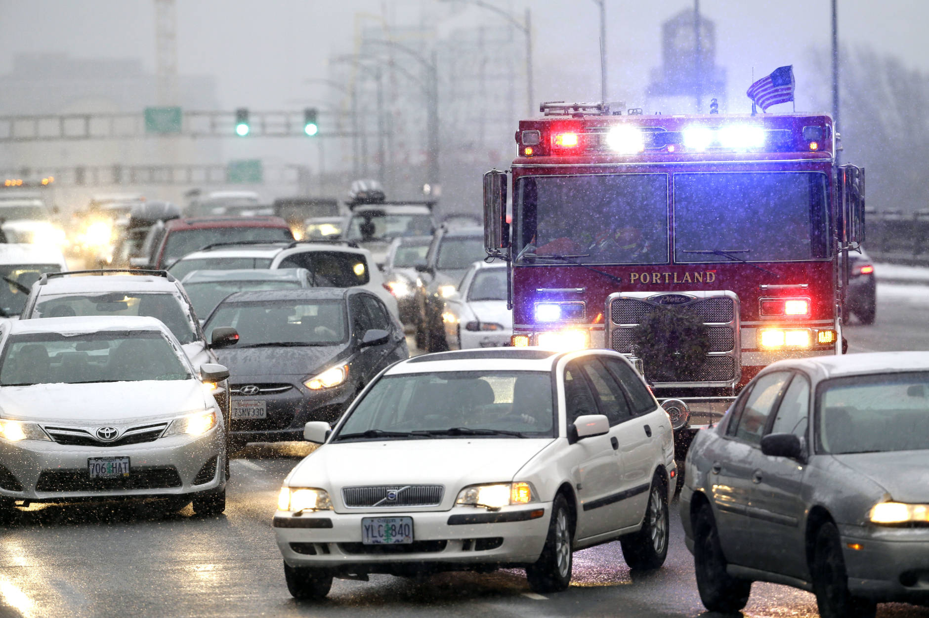An emergency vehicle fights through heavy traffic as a snow storm moves in on the area in Portland, Ore., Wednesday, Dec. 14, 2016. A wintry afternoon and evening is forecast for much of Oregon, with some cities expected to get a foot of snow.(AP Photo/Don Ryan)