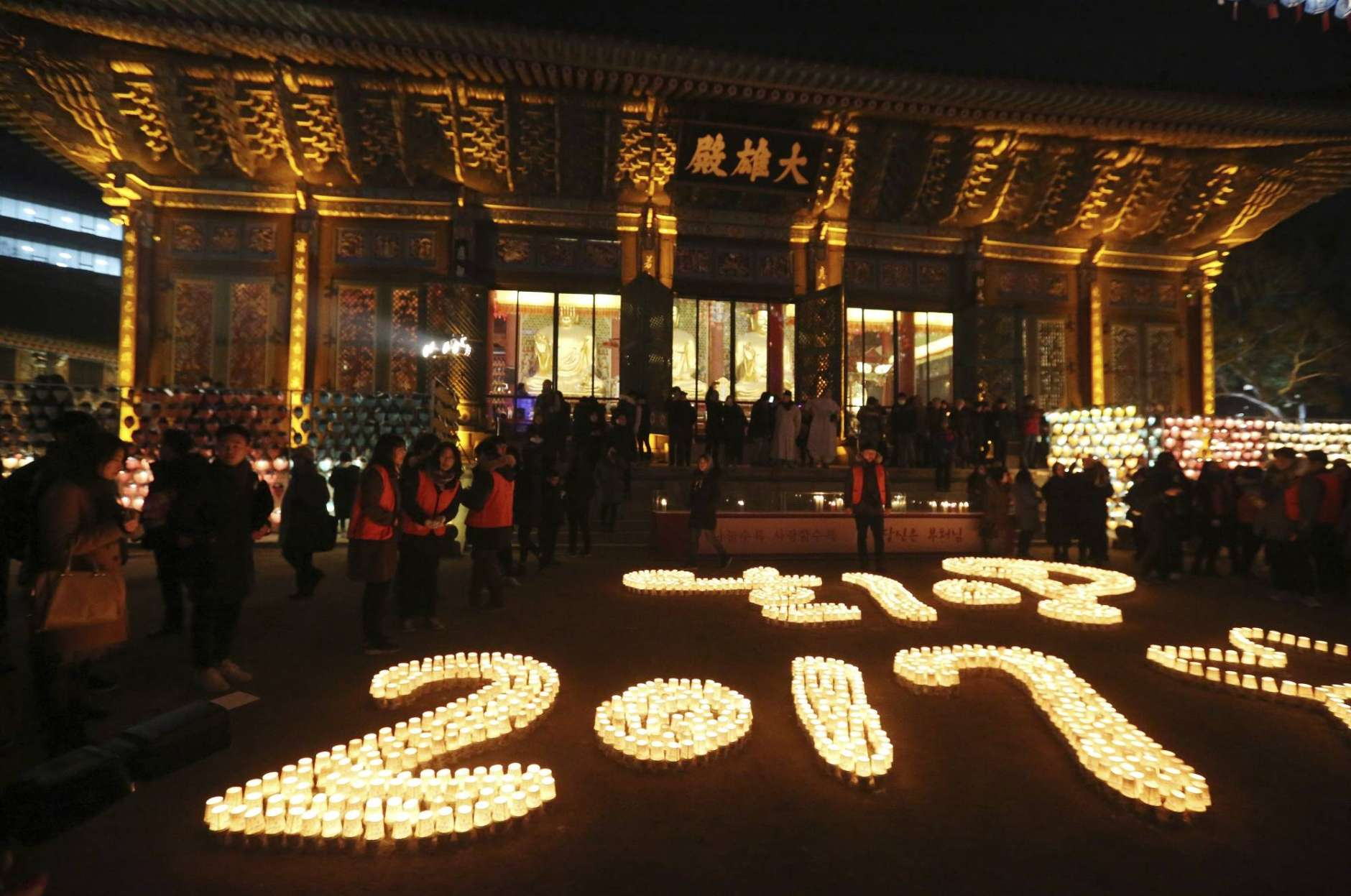 Buddhists light candles during New Year celebrations at Jogye Buddhist temple in Seoul, South Korea, early Sunday, Jan. 1, 2017. (AP Photo/Ahn Young-joon).