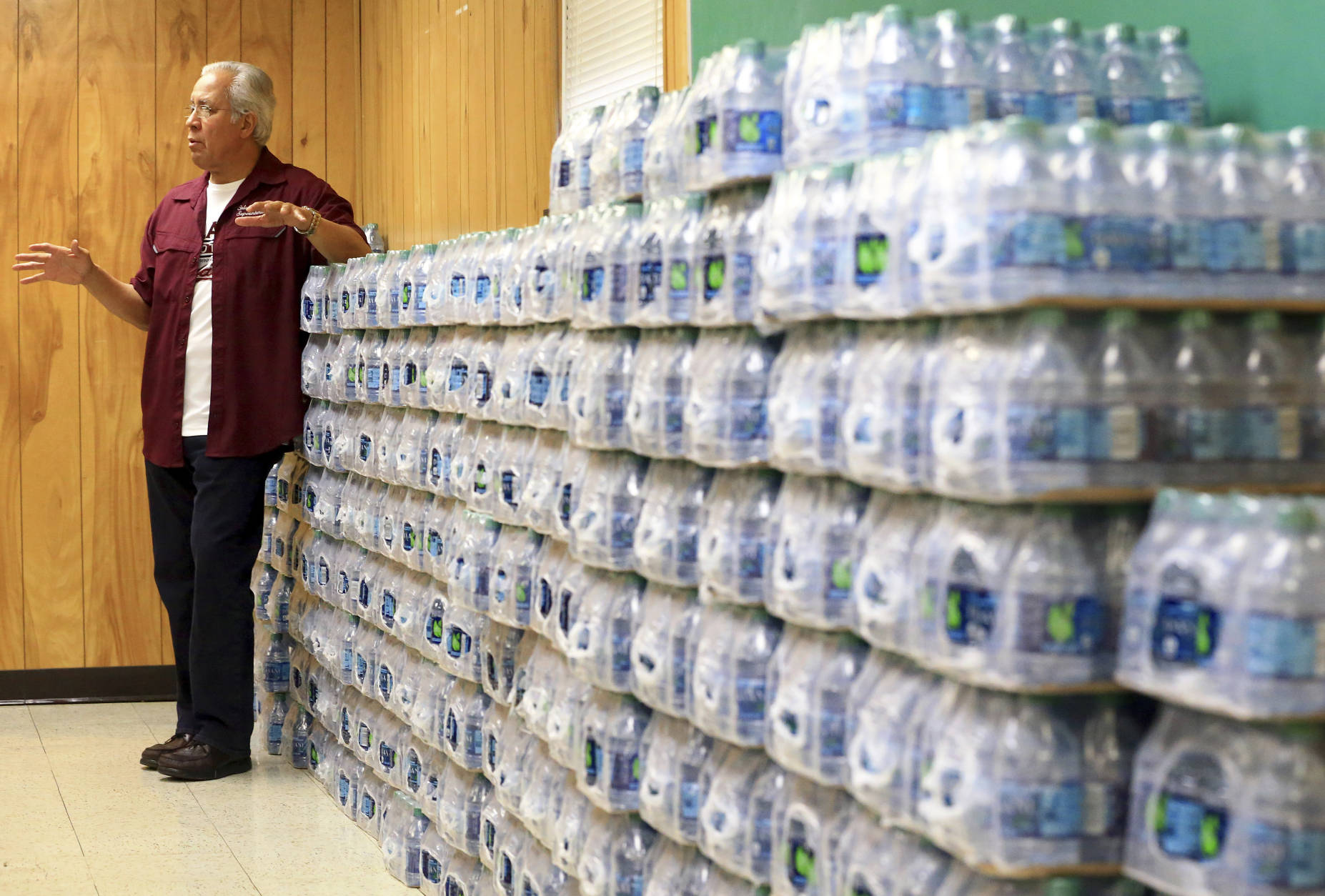 Superintendent Dr. Arturo Almendarez from Calallen Independent School District, speaks about how his district has bottles of water for students, Thursday, Dec. 15, 2016, in Corpus Christi, Texas. The city is warning its 320,000 residents not to use tap water because it might be contaminated with petroleum-based chemicals, prompting a rush on bottled water and the closure of local schools. (Gabe Hernandez/Corpus Christi Caller-Times via AP)