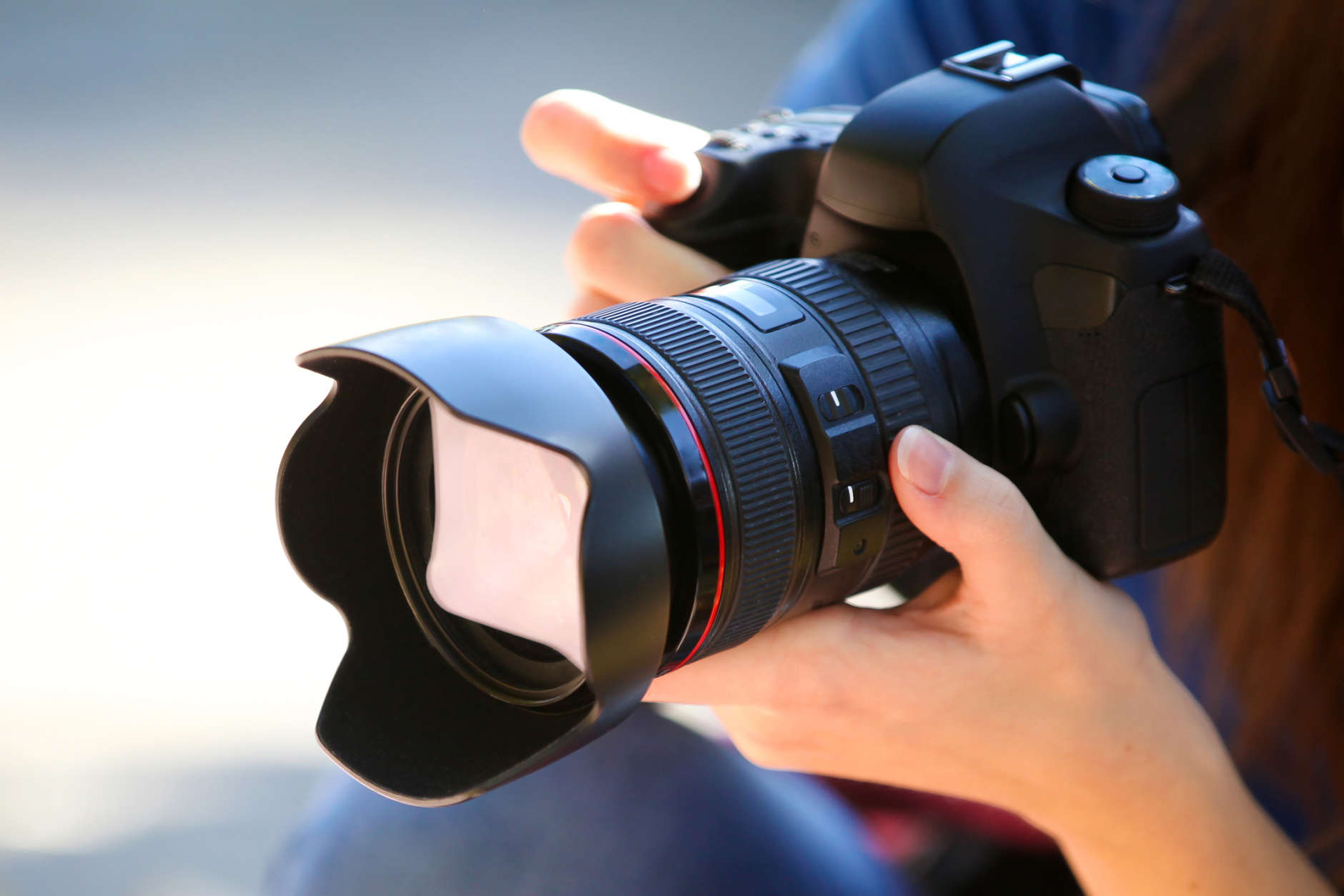 A Young Woman Holding a Full Frame Camera.