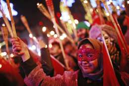People hold torches during New Year's cerebrations in Istanbul's Ortakoy district by the Bosphorus, during New Year's cerebrations, late Saturday, Dec. 31, 2016. (AP Photo/Emrah Gurel)