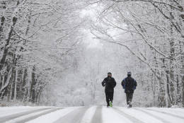 Ken Perry and Stan Ly go for a run in Eagle Creek Park as snow falls Tuesday, Dec. 13, 2016, in Indianapolis. (AP Photo/Darron Cummings)