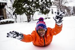 """Steven Washington, 9, dives faces first into a fresh pile of snow, taking a break from shoveling his grandmother's driveway after school was called off for a snow day Monday, Dec. 12, 2016, on Flint, Mich.'s north side. """"I like to see when the snow falls,"""" he said. """"I love to play in it and make snow angels. It was so cool to get out of school today so I could just be outside around so much snow."""" (Jake May/The Flint Journal-MLive.com via AP)"""
