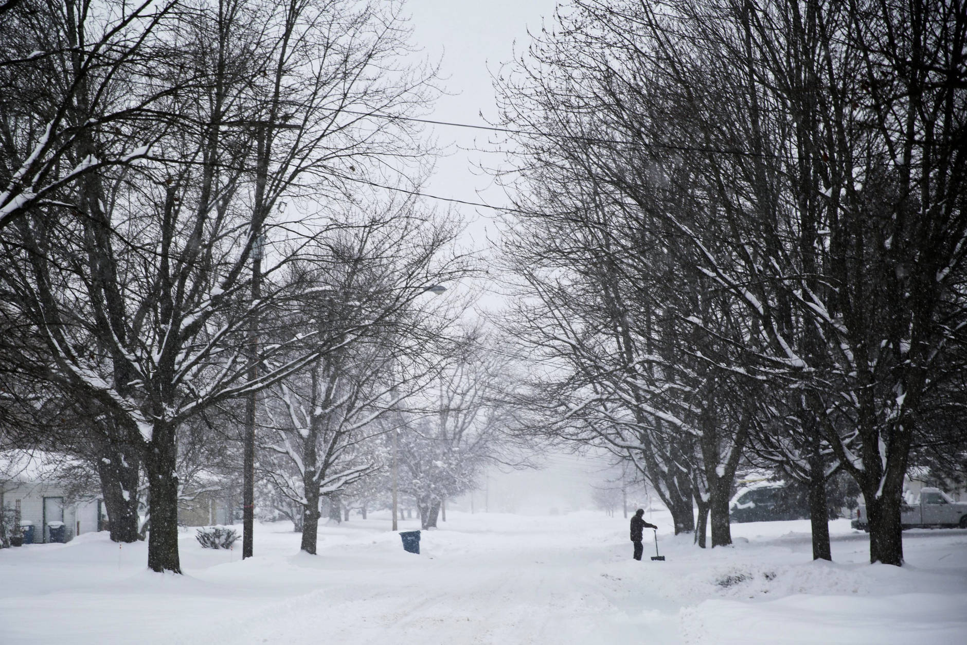 A man shovels the sidewalk in Kalamazoo, Mich., on Sunday, Dec. 11, 2016. Snow from snow showers earlier in the week have blanketed Kalamazoo with inches of snow. (Chelsea Purgahn/Kalamazoo Gazette-MLive Media Group via AP)