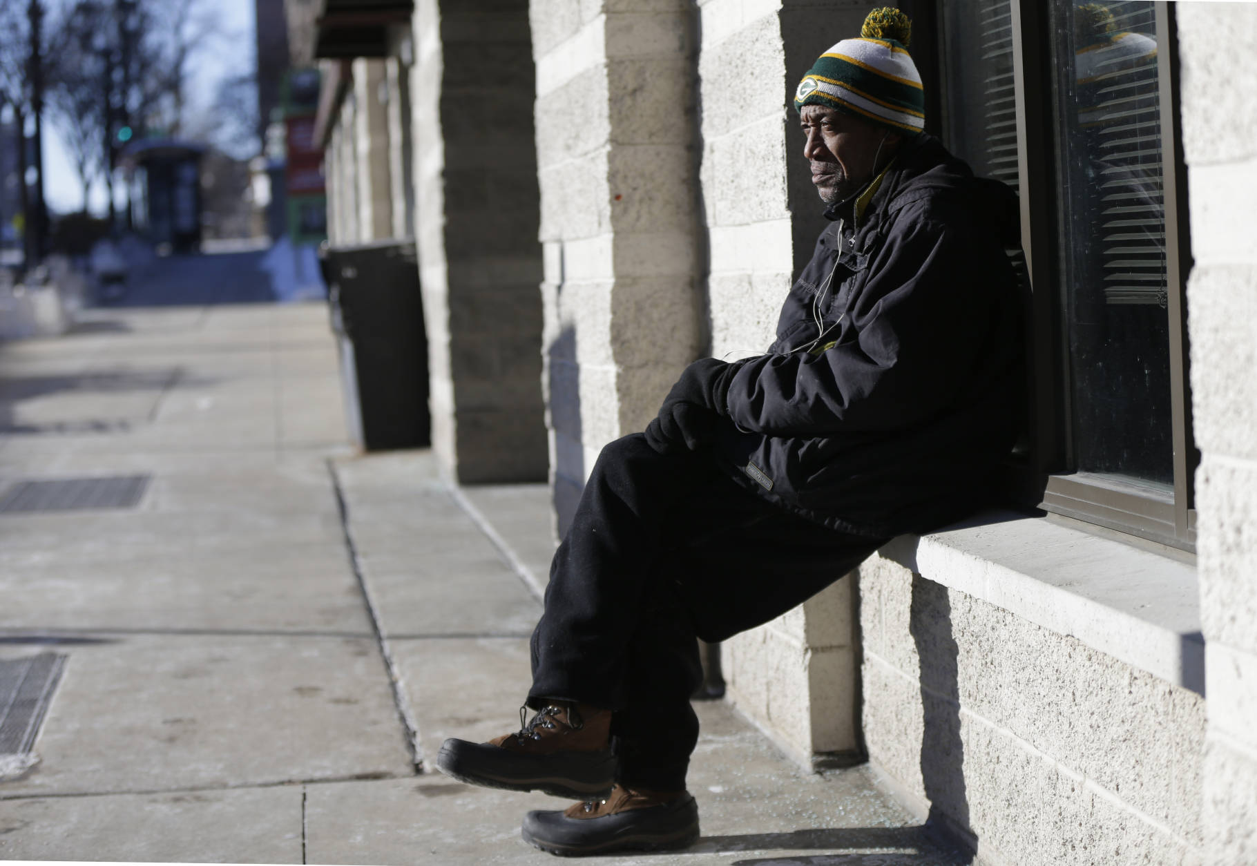 Kenneth High, who is homeless, sits outside a business on W. Wisconsin Ave. near N. James Lovell St. on Tuesday, Dec. 13, 2016, in Milwaukee, Wis. A blast of arctic air blew into Wisconsin Tuesday, dropping temperatures to dangerous levels. (Mike De Sisti  /Milwaukee Journal-Sentinel via AP)