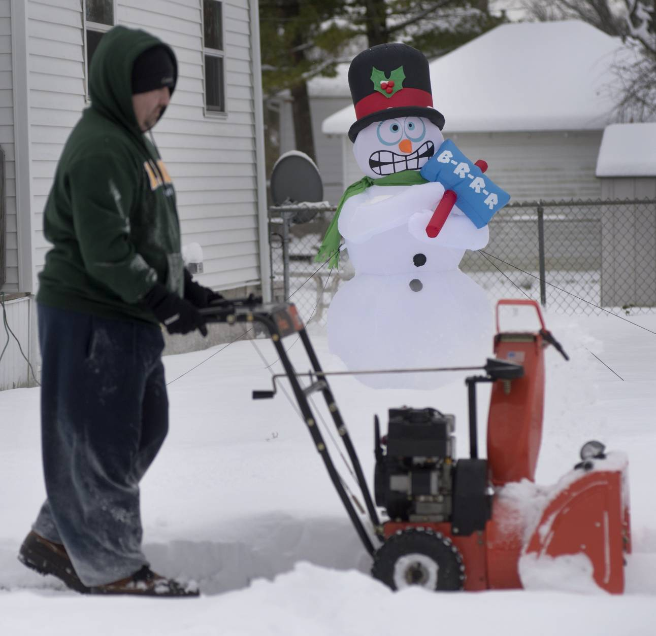 Dave Snell clears snow from the sidewalk in front of his Saginaw, Mich., home on Monday morning, Dec. 12, 2016. According to the National Weather Service, almost nine inches of snow fell on Saginaw on Sunday through Monday morning. All area schools are closed for the day. (Jeff Schrier/The Saginaw News via AP)